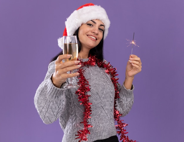 Glimlachend jong kaukasisch meisje met kerstmuts en klatergoudslinger om nek met vakantiesterretje en glas champagne uitrekkend naar geïsoleerd op paarse muur