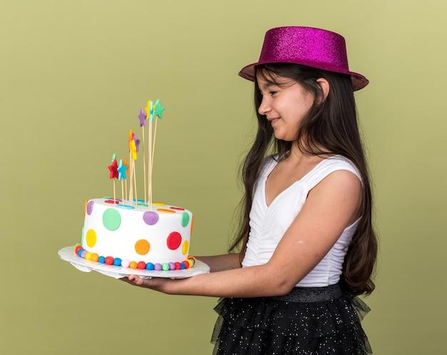 Glimlachend jong kaukasisch meisje met paarse feestmuts houden en kijken naar verjaardagstaart staande zijwaarts geïsoleerd op olijfgroene muur met kopie ruimte