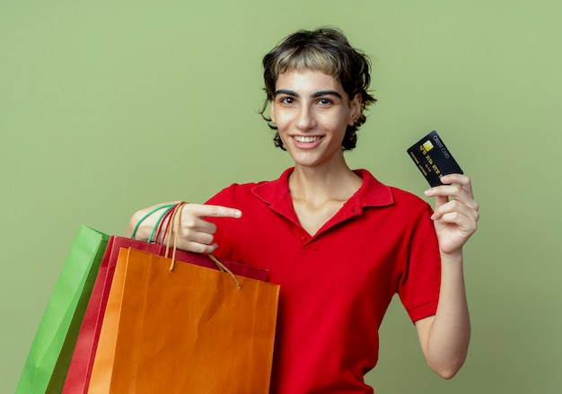 Glimlachend jong kaukasisch meisje met pixie-kapsel met boodschappentassen en creditcard wijzend op kaart op olijfgroene ruimte
