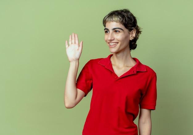 Glimlachend jong kaukasisch meisje met pixiekapsel die kant bekijken die hallo gebaar doen dat op olijfgroene achtergrond met exemplaarruimte wordt geïsoleerd