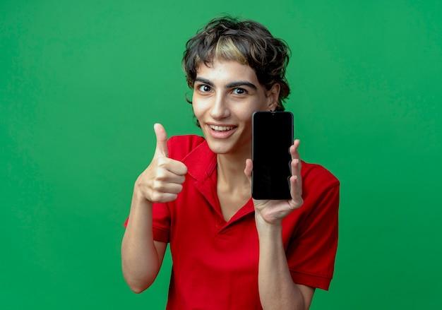 Glimlachend jong kaukasisch meisje met pixiekapsel die mobiele telefoon houden en duim tonen die omhoog op groene achtergrond met exemplaarruimte wordt geïsoleerd