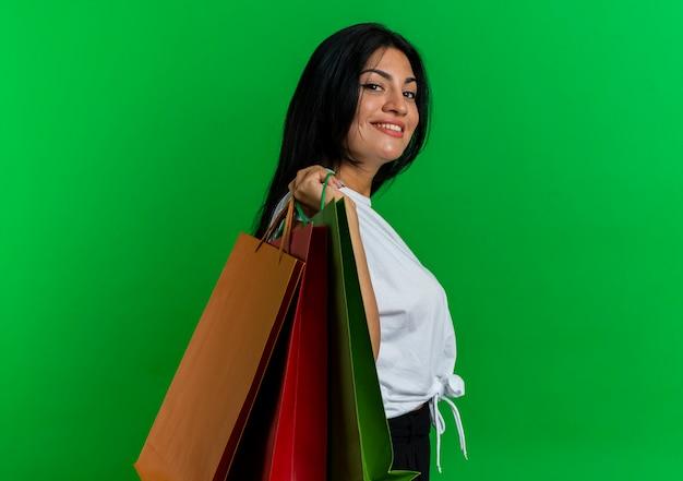 Glimlachend jong kaukasisch meisje staat zijwaarts met papieren boodschappentassen op de schouder