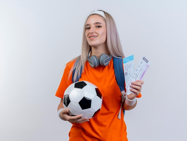 Glimlachend jong kaukasisch sportief meisje met hoofdtelefoons om hals die rugzakhoofdband draagt