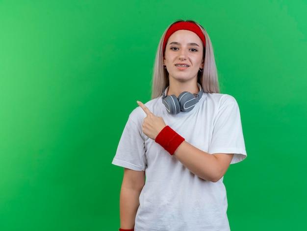 Glimlachend jong kaukasisch sportief meisje met steunen die hoofdband dragen