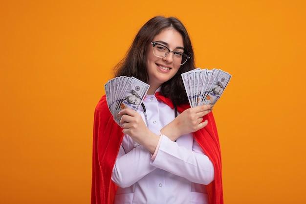 Glimlachend jong kaukasisch superheldenmeisje dat doktersuniform en stethoscoop draagt met een bril die de handen gekruist houdt en geld vasthoudt