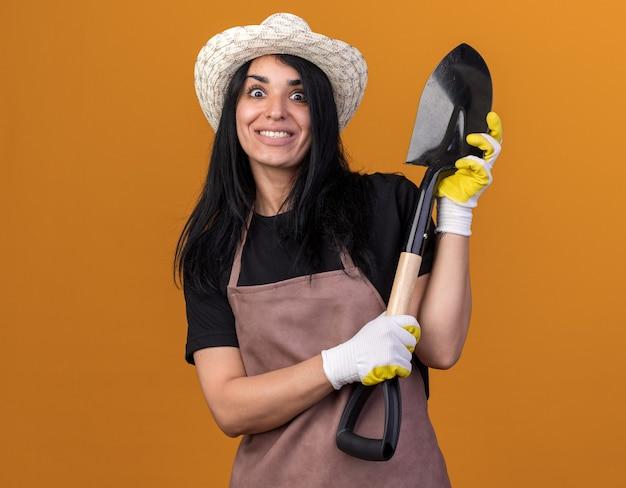 Glimlachend jong kaukasisch tuinmanmeisje dat uniform en hoed draagt met tuinmanhandschoenen die schop houden die op oranje muur met exemplaarruimte wordt geïsoleerd
