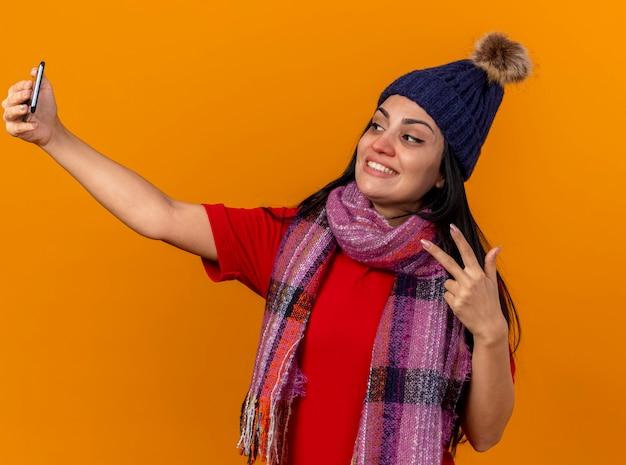 Glimlachend jong kaukasisch ziek meisje die de winterhoed en sjaal dragen die selfie nemen die vredesteken doen dat op oranje muur wordt geïsoleerd