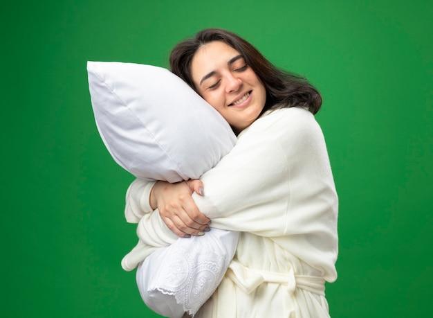 Glimlachend jong kaukasisch ziek meisje die gewaad dragen die zich in profielmening bevinden die hoofdkussen met gesloten ogen koesteren die op groene achtergrond wordt geïsoleerd