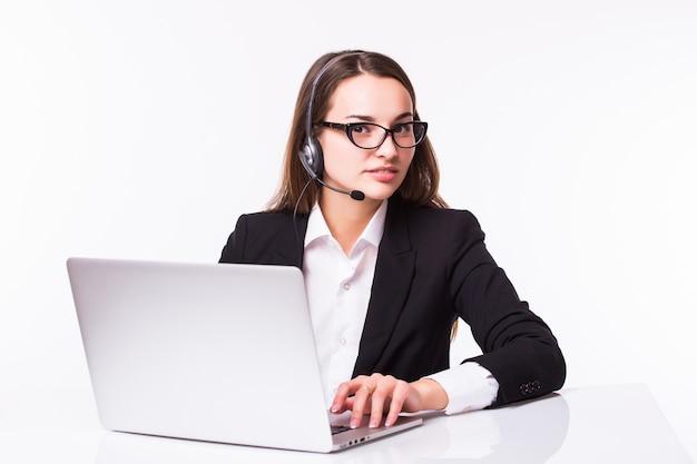 Glimlachend jong klantenservicemeisje met een hoofdtelefoon op haar die werkplek op wit wordt geïsoleerd