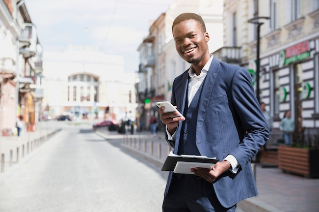 Glimlachend jong klembord van de zakenmanholding en mobiele telefoon die in hand zich op weg in stad bevinden