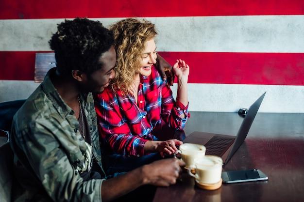 Glimlachend jong koppel in een coffeeshop met behulp van touchscreen computer. jonge man en vrouw in een restaurant kijken naar digitale tablet.