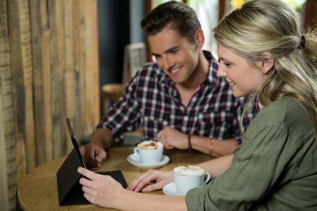 Glimlachend jong koppel met behulp van digitale tablet aan tafel in de coffeeshop