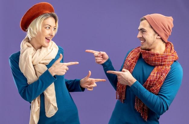 Glimlachend jong koppel met hoed met sjaal op valentijnsdag kijken en wijzen naar elkaar geïsoleerd op blauwe achtergrond