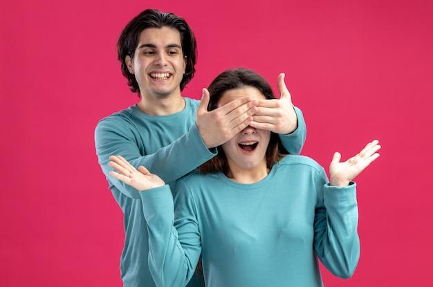 Glimlachend jong koppel op valentijnsdag jongen bedekt meisjes ogen met handen geïsoleerd op roze achtergrond