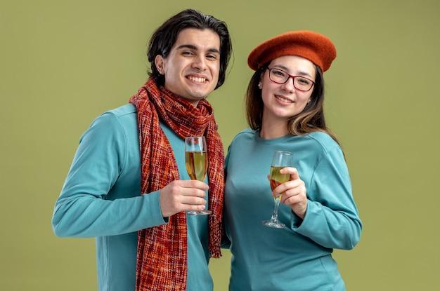 Glimlachend jong koppel op valentijnsdag man met sjaal meisje met hoed met glas champagne geïsoleerd op olijf groene achtergrond