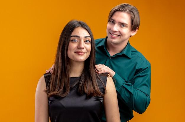 Glimlachend jong koppel op valentijnsdag man staande achter meisje hand op schouder geïsoleerd op oranje achtergrond