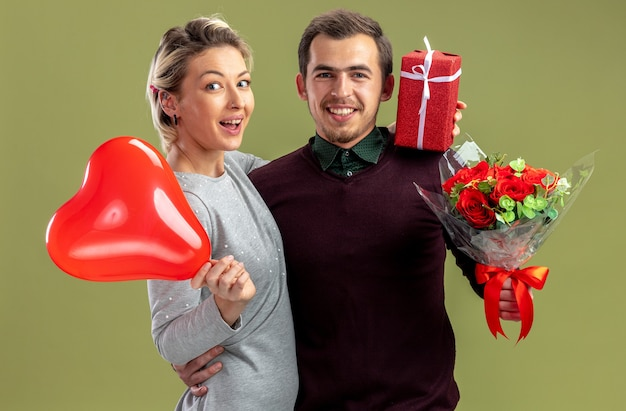 Glimlachend jong koppel op valentijnsdag omhelsde elkaar met hartballon met geschenken geïsoleerd op olijfgroene achtergrond