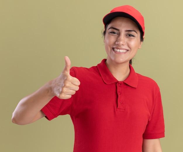 Glimlachend jong leveringsmeisje dat uniform draagt met dop die duim toont geïsoleerd op olijfgroene muur