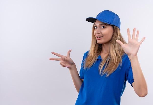 Glimlachend jong leveringsmeisje die blauwe uniform en pet verschillende gebaren dragen die op witte muur met exemplaarruimte worden geïsoleerd