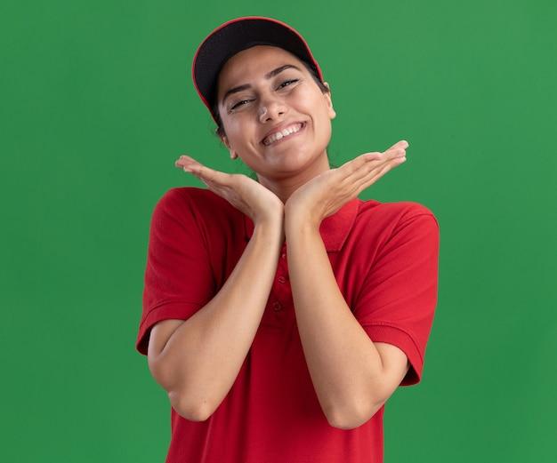 Glimlachend jong leveringsmeisje die eenvormig en glb dragen die handen rond gezicht dragen dat op groene muur wordt geïsoleerd