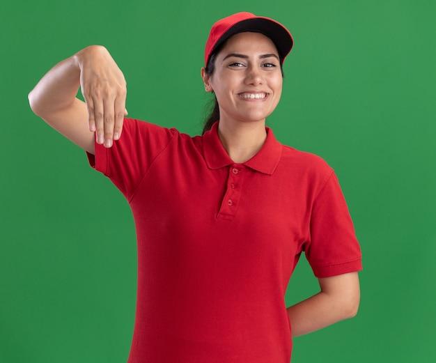 Glimlachend jong leveringsmeisje die eenvormig en glb dragen die iets houden dat op groene muur wordt geïsoleerd beweren