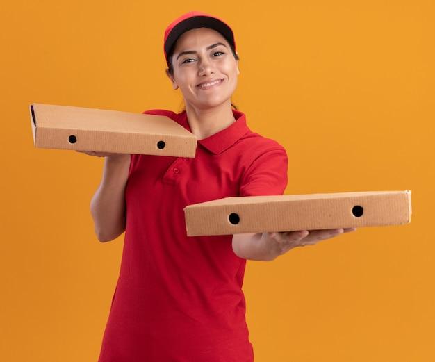Glimlachend jong leveringsmeisje die eenvormig en glb dragen die pizzadozen aan voorzijde houden die op oranje muur worden geïsoleerd