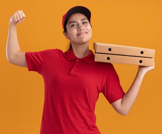 Glimlachend jong leveringsmeisje die eenvormig en glb dragen die pizzadozen houden die sterk gebaar tonen dat op oranje muur wordt geïsoleerd