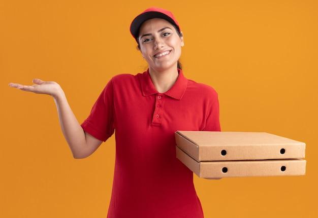 Glimlachend jong leveringsmeisje die eenvormig en glb dragen die pizzadozen verspreiden die hand verspreiden die op oranje muur wordt geïsoleerd