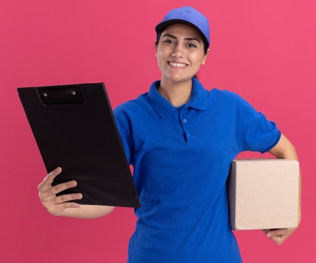Glimlachend jong leveringsmeisje die eenvormig met de doos van de glbholding dragen en klembord aan voorzijde houden die op roze muur wordt geïsoleerd