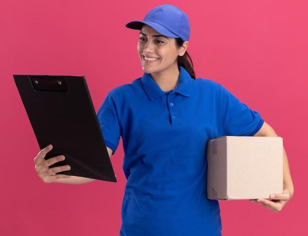 Glimlachend jong leveringsmeisje die eenvormig met de doos van de glbholding dragen en klembord in haar hand bekijken dat op roze muur wordt geïsoleerd