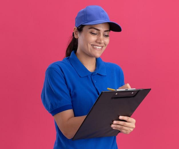 Glimlachend jong leveringsmeisje die eenvormig met glb dragen die iets op klembord schrijven dat op roze muur wordt geïsoleerd
