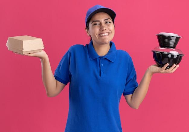 Glimlachend jong leveringsmeisje die eenvormig met glb dragen die voedselcontainers houden die op roze muur worden geïsoleerd