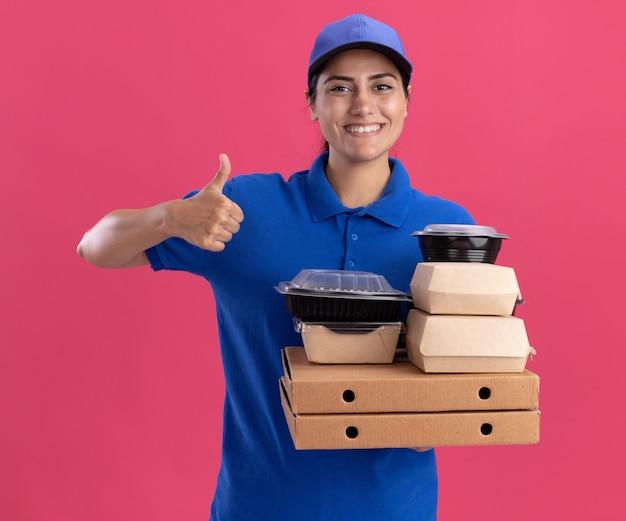 Glimlachend jong leveringsmeisje die eenvormig met glb dragen die voedselcontainers op pizzadozen houden die duim tonen die omhoog op roze muur wordt geïsoleerd