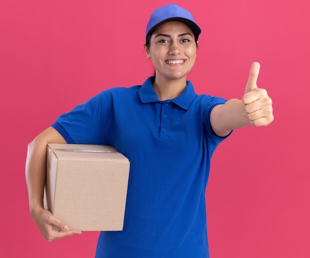 Glimlachend jong leveringsmeisje die eenvormig met glb-holdingsdoos dragen die duim tonen die omhoog op roze muur wordt geïsoleerd