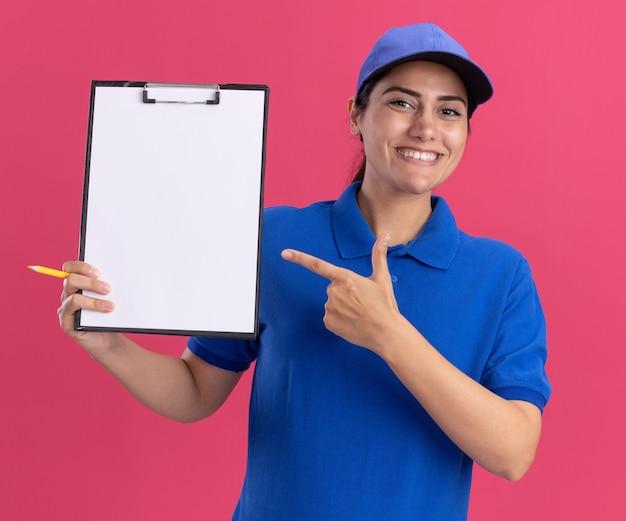 Glimlachend jong leveringsmeisje die eenvormig met glbholding dragen en wijst op klembord dat op roze muur wordt geïsoleerd