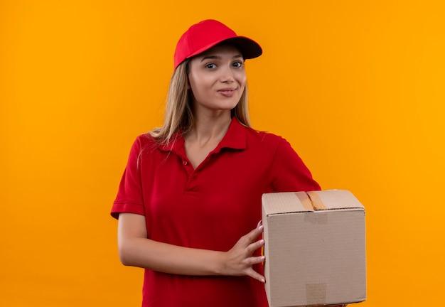 Glimlachend jong leveringsmeisje die rode eenvormig en glb-holdingsdoos dragen die op oranje muur wordt geïsoleerd
