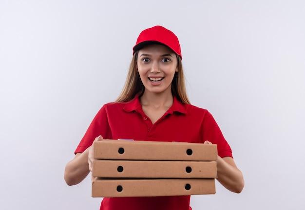 Glimlachend jong leveringsmeisje die rood uniform dragen en de pizzadoos van de glbholding op wit wordt geïsoleerd