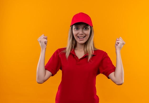 Glimlachend jong leveringsmeisje die rood uniform en glb dragen die ja gebaar tonen dat op oranje muur wordt geïsoleerd