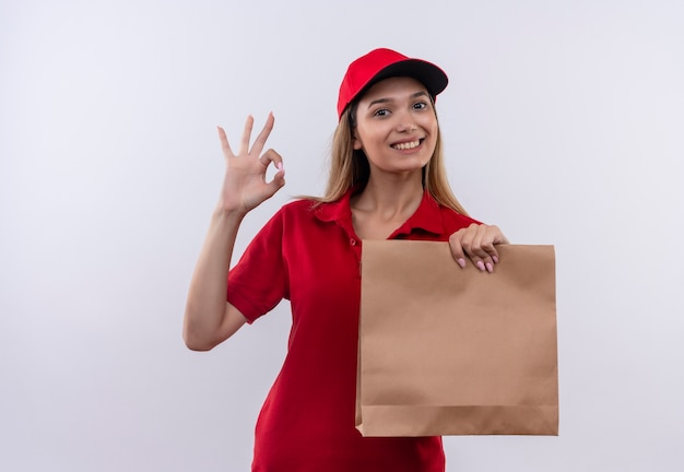 Glimlachend jong leveringsmeisje die rood uniform en glb dragen die papieren zak houden en okey gesrure tonen die op wit wordt geïsoleerd