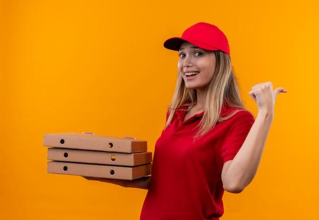 Glimlachend jong leveringsmeisje die rood uniform en glb dragen die pizzadoos houden en naar kant wijzen die op oranje muur wordt geïsoleerd