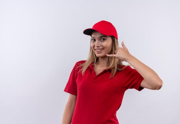 Glimlachend jong leveringsmeisje die rood uniform en glb dragen die telefoongesprekgebaar tonen dat op wit wordt geïsoleerd