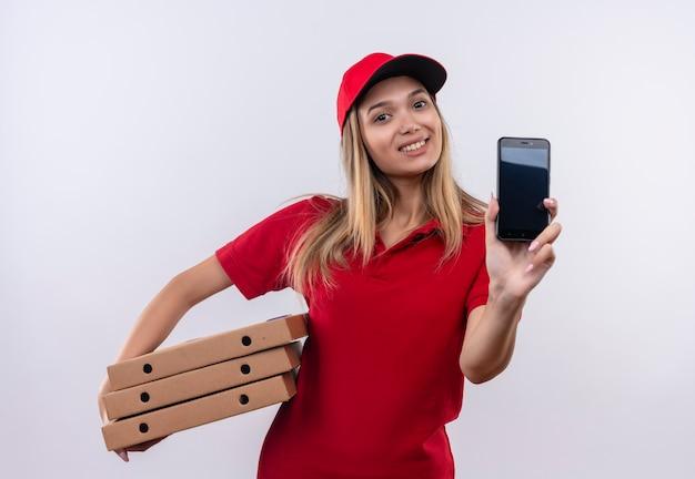 Glimlachend jong leveringsmeisje die rood uniform en pet dragen die telefoon en pizzadoos op wit wordt geïsoleerd