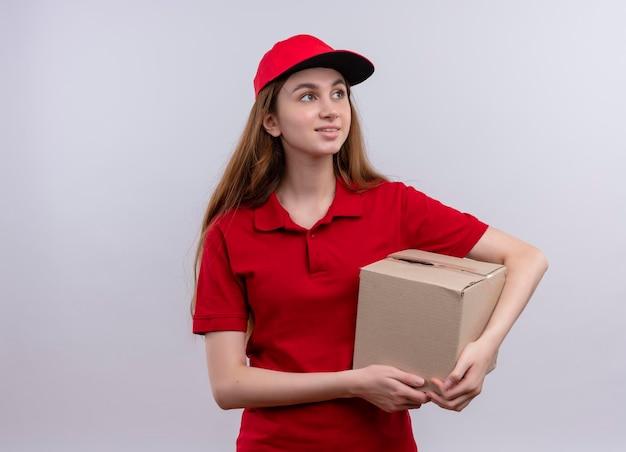 Glimlachend jong leveringsmeisje in rode eenvormige holdingsdoos die rechterkant op geïsoleerde witte ruimte met exemplaarruimte bekijken