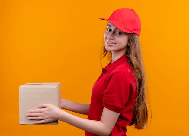 Glimlachend jong leveringsmeisje in rode eenvormige holdingsdoos die zich in profielmening op geïsoleerde oranje ruimte bevinden