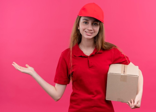Glimlachend jong leveringsmeisje in rode eenvormige holdingsdoos en lege hand op geïsoleerde roze ruimte tonen