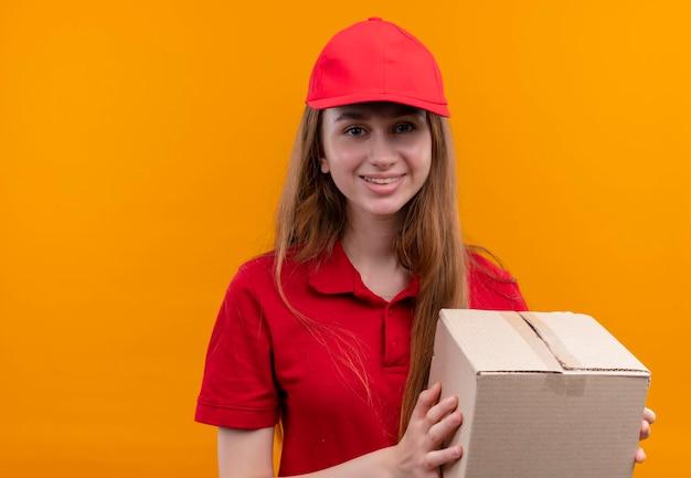 Glimlachend jong leveringsmeisje in rode eenvormige holdingsdoos op geïsoleerde oranje ruimte met exemplaarruimte