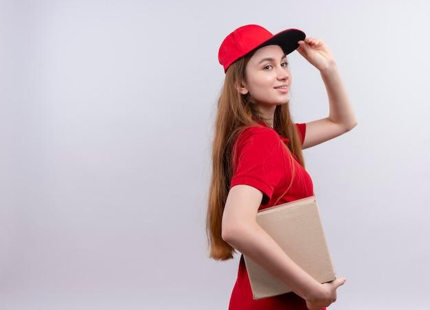 Glimlachend jong leveringsmeisje in rode uniforme holdingsdoos en hand op glb zetten die zich in profielmening bevinden op geïsoleerde witte ruimte met exemplaarruimte