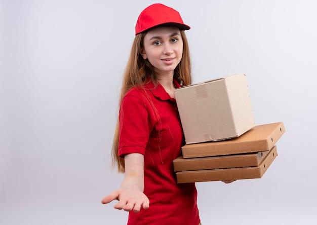 Glimlachend jong leveringsmeisje in rode uniforme holdingsdoos en pakketten en hand uitrekken op geïsoleerde witte ruimte met exemplaarruimte