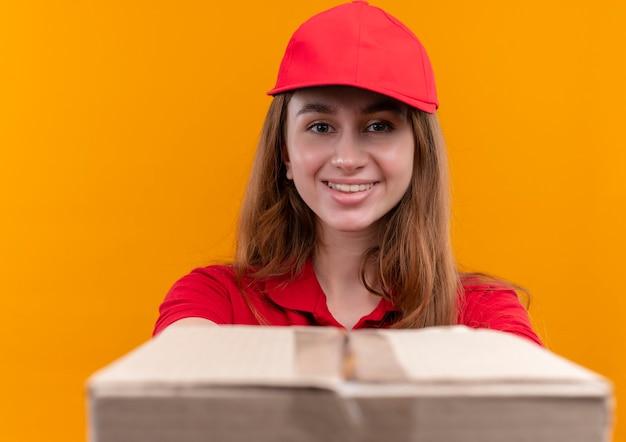 Glimlachend jong leveringsmeisje in rood eenvormig uitrekkende doos op geïsoleerde oranje muur