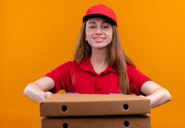 Glimlachend jong leveringsmeisje in rood uniform die pakketten op geïsoleerde oranje muur uitrekken